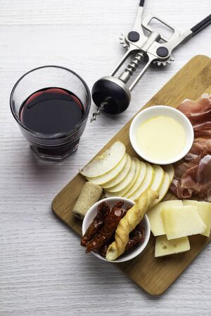 red wine and snacks, corkscrew on white background Фото со стока
