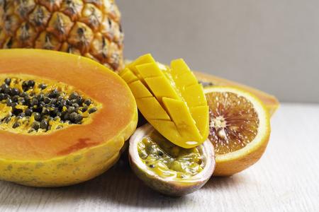 tropical fruits: papaya, pineapple, mango, passion fruit on a gray background close-up Archivio Fotografico
