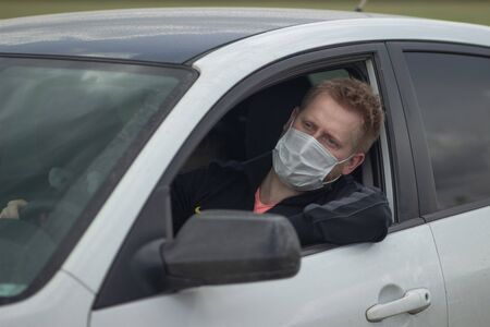 Light man with blue eyes in a medical mask behind the wheel of a car