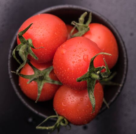 some red fresh tomato cherry in black  bowl on dark gray background macro close up top view Stock Photo