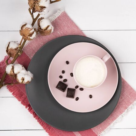 coffee latte on the pink and gray pastel plate with chocolate and branch cotton wood background coral napkin top view Stok Fotoğraf