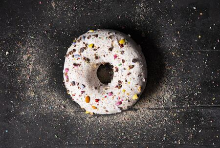 single delicious donut on dark background with colorful sprinkle concept art top view Stok Fotoğraf