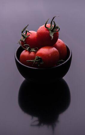 some red fresh tomato cherry in black  bowl on dark gray mirror background macro close up shaddow Stock Photo