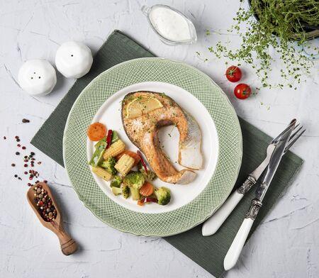 leckeres rotes Fischsteak mit Gemüse in der Draufsicht des grünen Telleressens