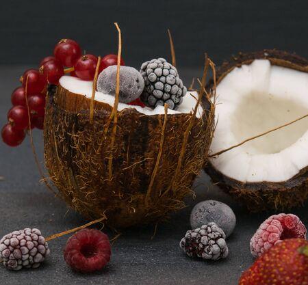 frozen berries redberry red currant on half coconut dessert fresh dark background front
