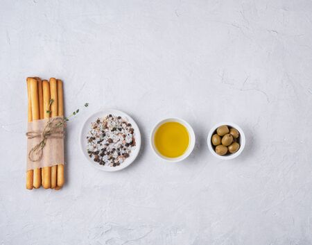 italian grissini stick bread with salt, olive oli and thyne on white beton table top view
