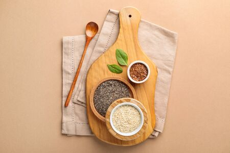 Some different bowls with  vegan superfood cereal chia, sesame and linum on cutting board on beige background. Image is top view, flat lay and copy space Reklamní fotografie
