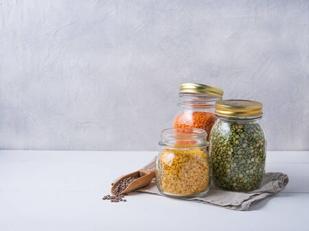 Three jar with yellow, orange and green  lentil with wooden spoon stay on white table.Image is  front view and copy space