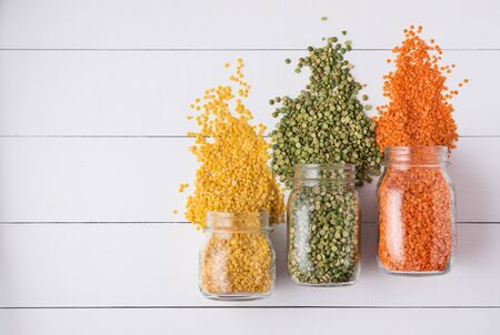 Three jar with yellow, orange and green  lentil scatter on white wooden  table. Image is top view and copy space Фото со стока