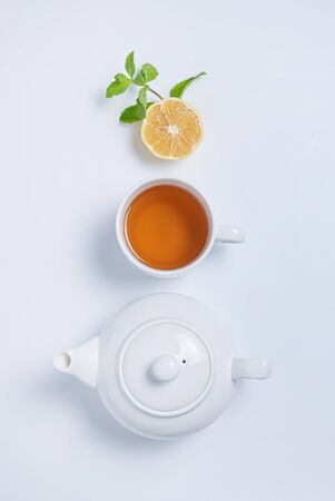 Fresh aroma cup of black tea and tea pot with lemon, mint and golden spoon on white  background. Top view and copy space. Vertical orientation.