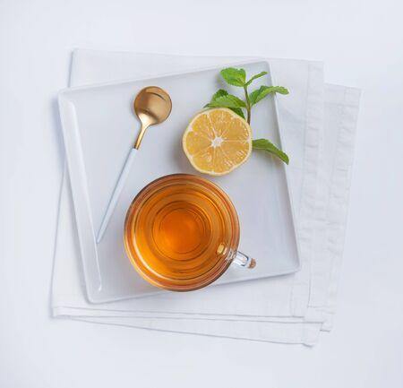 Fresh aroma cup of black tea with lemon, mint and golden spoon on square white plate and  white background. Top view