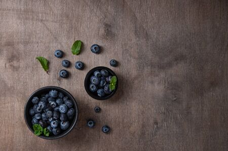 Fresh and sweet blueberry in two black bowls with mint on brown wood background. Top view and copy space Foto de archivo - 135502100