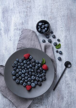 Fresh and sweet blueberry and raspberry in gray  plate and napkin on old vintage  white wood background. Top view and copy space. Foto de archivo - 135502430