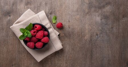Fresh and sweet raspberry with mint in  black bowl on old vintage brown wood background. Top view and copy space. Foto de archivo - 135502093