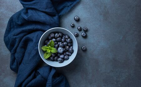 Fresh and sweet blueberry in  bowl with mint and  classic blue napkin on dark wood background. Top view and copy space Foto de archivo - 135502147