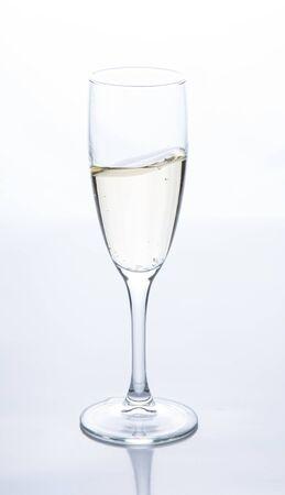 sobre la mesa hay una copa de champán espumoso. Luz de contorno. Vista frontal Foto de archivo