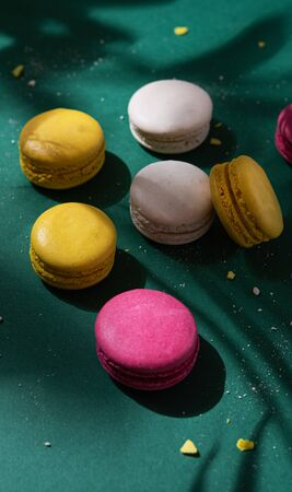 a few delicious colorful macaron with deep shadow on a green background.