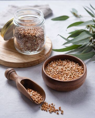 green vegan buckwheat in a wooden bowl , spoon and glass jar on a light grey background. Superfood and diet food