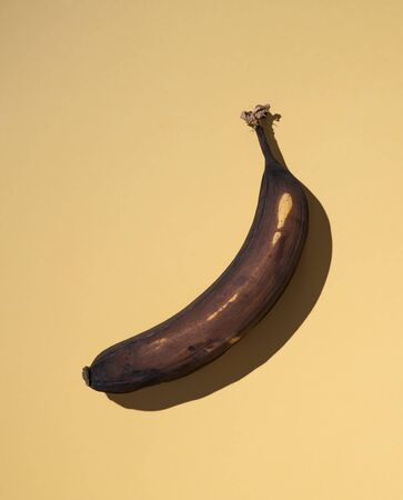 a spoiled and ugly black banana on a yellow background with a hard shadow. Concept photo. Top view and copy space Stock fotó