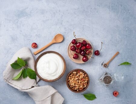 natural healthy superfood fermented yogurt with granola, chia seeds and cherry on light table. copy space and top view Reklamní fotografie