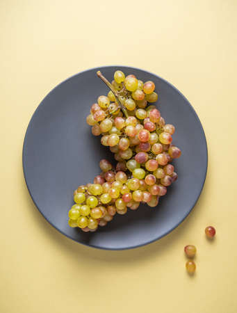 a cluster of juicy green pink grapes in a gray plate  on a yellow background.  Top view and copy space 免版税图像