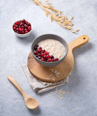Oatmeal porridge bowl with cranberries on the cutting board on light gray background. Healthy, dieting and energy breakfast. 免版税图像
