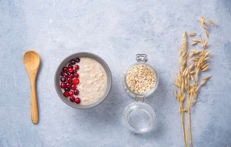 Healthy oats porridge with cranberries on light blue background with jar flakes and oatmeal ears. Healthy breakfast diet food. Top view, flat lay and copy space concept 免版税图像