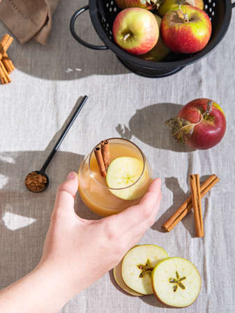Hand hold a glass of freshly brewed apple drink with apple slices and cinnamon on linen tablecloth. Top view and flat lay 免版税图像