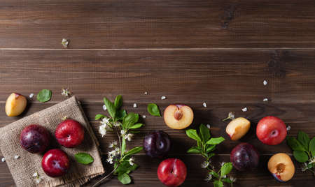 concept flat lay a few juicy red plums with branch blossom flowers on a brown wood background. Top view and copy space image
