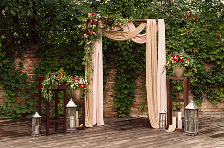arch for the wedding ceremony, decorated cloth flowers greenery, Stockfoto