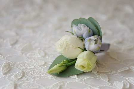Wedding boutonniere flower roses and blue delphinium white ribbon close up