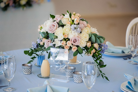 blue candles: Wedding table decorated with a bouquet of flowers roses and delphinium. Tablecloth blue candles and glass solfetka close