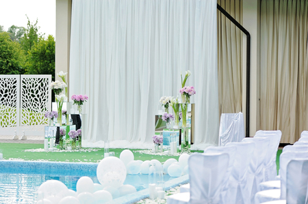 swimming candles: Decorations for the wedding ceremony by the pool with blue water.