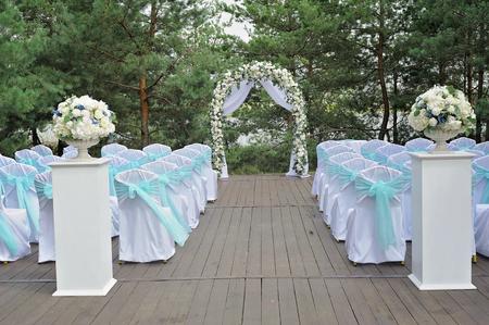 美しい結婚式のアーチ、花、椅子飾られています。