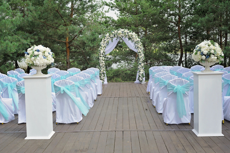 Beautiful wedding ceremony decorated with arch, flowers and chairs. Archivio Fotografico