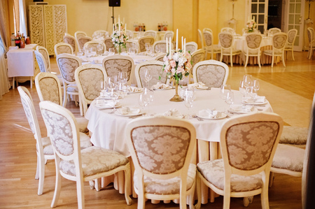 Guest tables with candlestick in rich decorated wedding banquet room