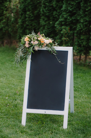 Chulk board, which stands on the grass for wedding inscription. Decorated with bouquet