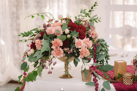Wedding table decoration with the red and pink flowers on the white cloth