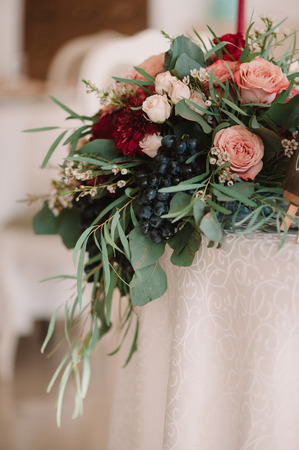 Autumnal wedding composition of roses, apples, grape and pomergranate