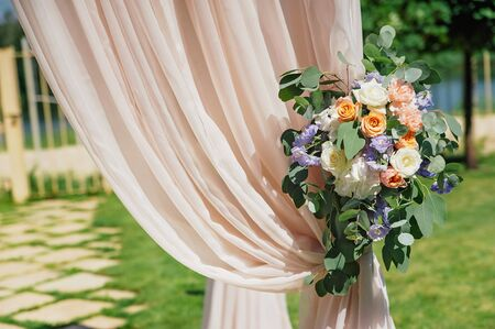 Beautiful wedding arch, decorated with biege cloth and flowers, closeup