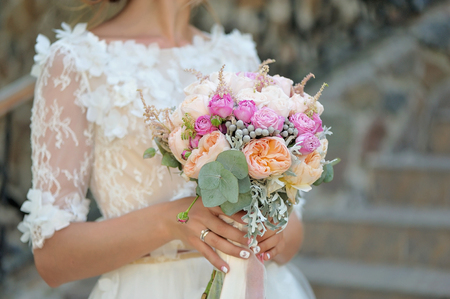 Bride holding delicate marriage bouquet
