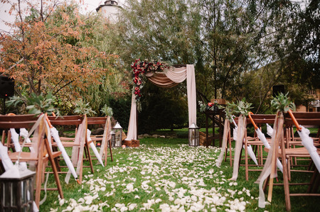 Autumnal wedding archway decoration of roses, apples, grape and pomergranate