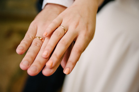 Newlyweds staying arm in arm, with wedding rings