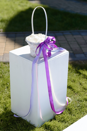 Wedding white basket decorated with violet ribbon
