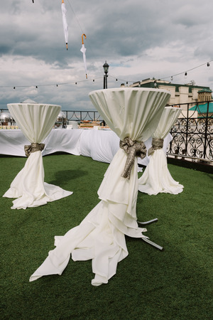 Empty decorated tables with bow knots for the wedding ceremony on roof Stock Photo