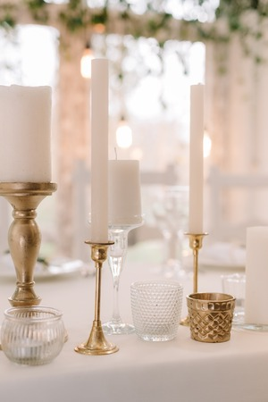 White candles on a wedding table. Gentle and stylish details of decoration of a wedding celebration