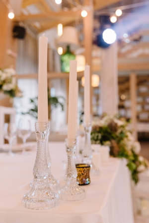 Thin glass candlesticks with ong white candles.