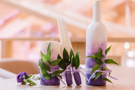Violet wedding candles and the decorated champagne bottle. Wedding accessories 스톡 콘텐츠