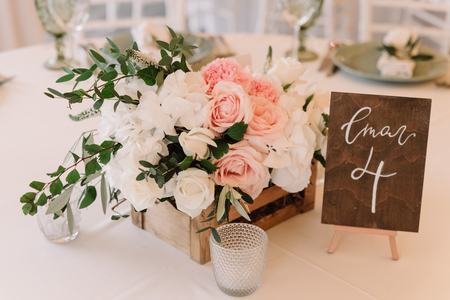 Lovely details decoration of a beautiful and stylish wedding: flowers in a wooden box and number of a table