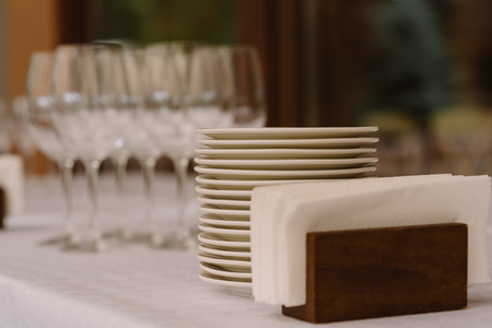 White napkins, plates against the background of glasses.